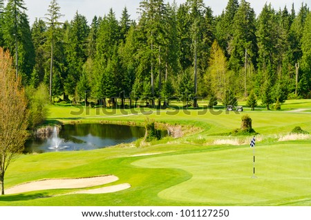 Golf place with gorgeous green and pond.