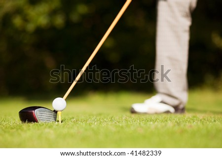 Golf player attempting the first stroke in the teeing area (only legs of player to be seen, focus on ball)