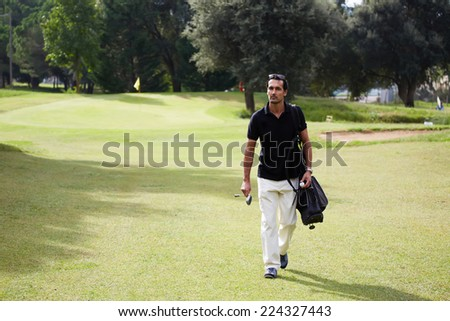Golf player carrying his bag and walking on a sunny day at golf course,confident man at golf game walk on beautiful golf course holding bag and driver,professional golf player walking to the next hole