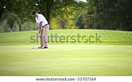 Golf player concentrating for putting golf ball on green.