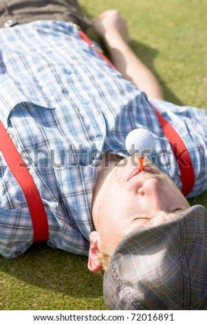 Golf Player Focused On His Game Directs His Energies Positively Before The Game By Meditating With A Golf Ball And Tee In His Mouth To Find His Inner Balance
