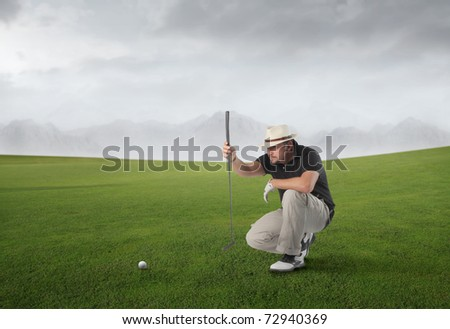Golf player on a green meadow observing a golf ball