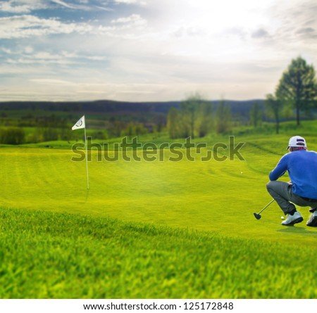 Golf player on the putting green aiming for putt
