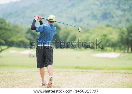 Golf player teeing off golf ball from tee box