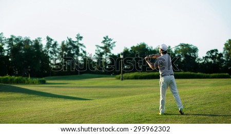 Golf player teeing off. Man hitting golf ball from tee box with driver isolated on sunny green golf course.