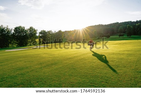 Golf player walking and bag on course during summer golf game in soft focus at sunlight. Sport playground for golf club concept - wide landscape as background for your lettering about golf playing. Foto stock ©