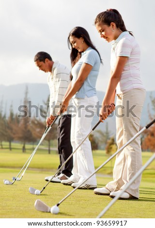 Golf players practicing to hit the ball at the course