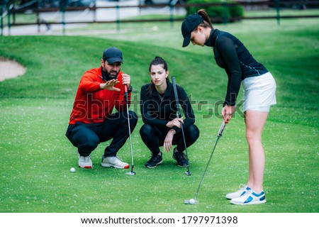 Golf putting lesson, two young female golfers practicing putting with golf instructor Photo stock ©