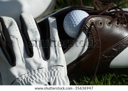 golf shoe, golf ball and glove on grass