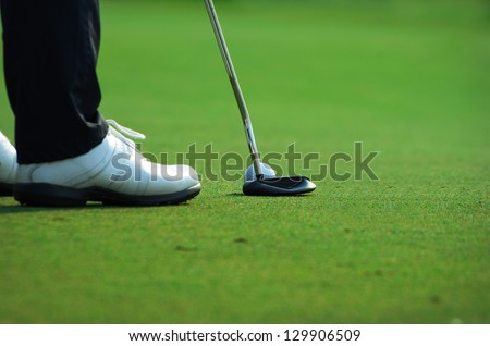 Golf stance while preparing to shoot. At the teeing ground