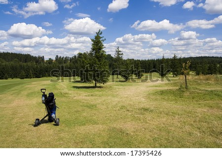 golf trolley standing on fairway of a beautiful golf course with dramatic summer sky