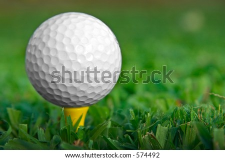 Golfball on yellow tee.