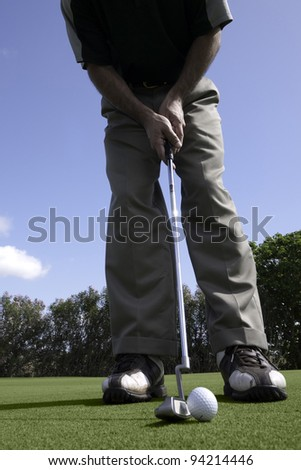 Golfer addresses a golf ball with a putter on the putting green.