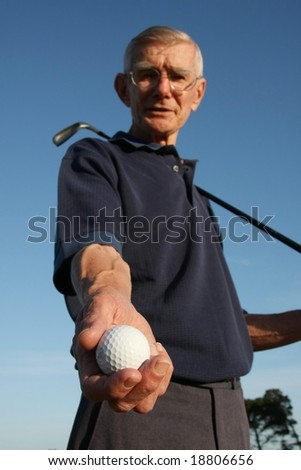 Golfer against blue sky showing his white gold ball
