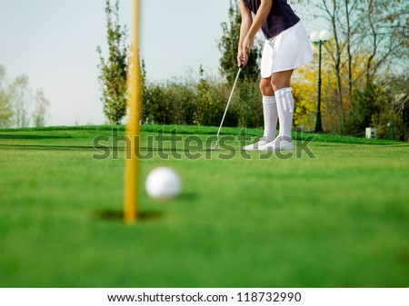 golfer and his ball just inches from the hole