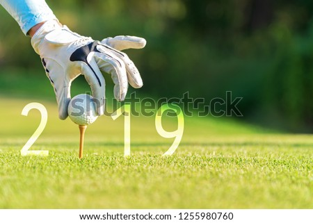 Golfer asian woman putting golf ball for Happy New Year 2019 on the green golf, copy space. Healthy and Holiday Concept.