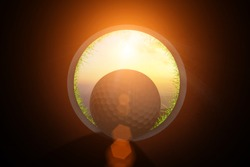Golfer at golf ball view from inside the hole of cup in the green golf club play and lens flare on sun set evening time gold sky background.