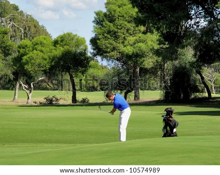 Golfer chipping onto the green on a beautiful sunny day.