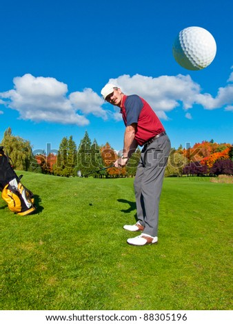 Golfer driving golf ball on beautiful golf course with deep blue sky and white clouds