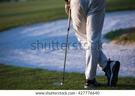 golfer  from back looking to ball and  hole in distance, handsome middle eastern golf player portrait from back with beautiful sunset in background #427776640