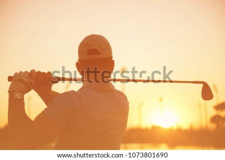 golfer hitting long shot with driver on course at beautiful sunset #1073801690