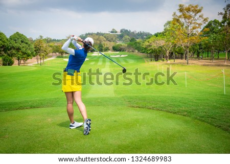 golfer is teeing off golf ball by golf club from tee boxes at golf course in golf competition game with white cloud sky background.