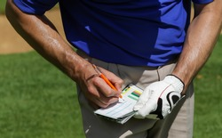 Golfer keeping score on scorecard