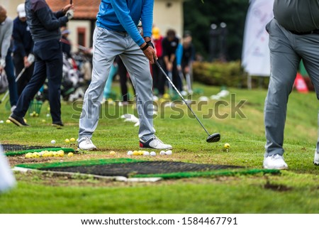 Photo of  Golfer legs at golf tournament practice swing with golf club. Golf players on green lawn putting golf ball in the hole. Golfing competition or tournament.