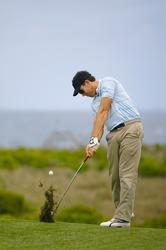 Golfer plays an iron shot from the fairway