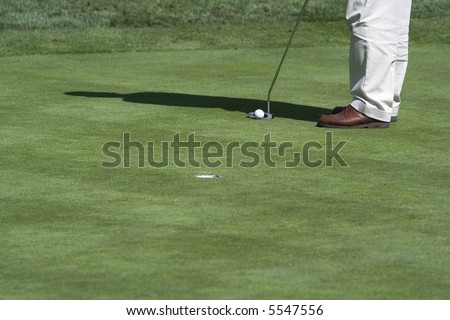 Golfer putting (ball by club)