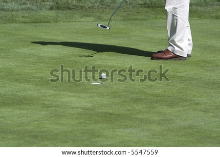 Golfer putting (ball by hole)