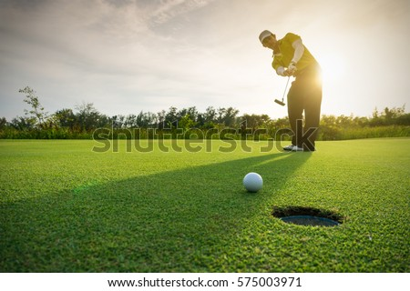golfer putting golf ball on the ...