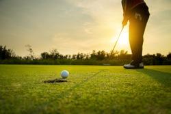 Golfer putting golf ball on the green golf, on sun set evening time.
