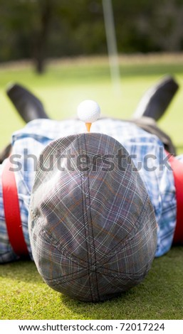 Golfer Relaxes Laying Down On A Golf Green Near The Ninth Hole With A Golf Tee And Golf Ball In His Mouth In A Sporting Concept With Copyspace On His Flat Cap