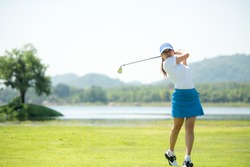 Golfer sport course golf ball fairway. People lifestyle woman playing game golf and hitting go on green grass river and mountain background. Asia female player game shot in summer. Healthy  Sport
