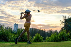 Golfer sport course golf ball fairway. People lifestyle woman playing game golf tee of on the green grass sunset background. Asia female player game shot in summer. Healthy and Sport outdoor