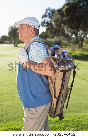 Golfer standing holding his golf bag on a sunny day at the golf course