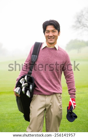 Golfer standing holding his golf bag smiling at camera at the golf course