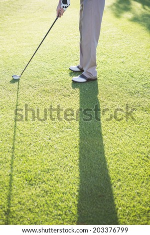 Golfer standing on the putting green on a sunny day at the golf course