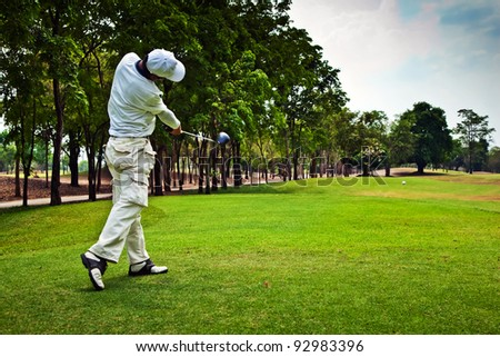 Golfer swinging his gear and hit the golf ball from tee to the fairway.
