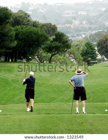 Golfer swings.