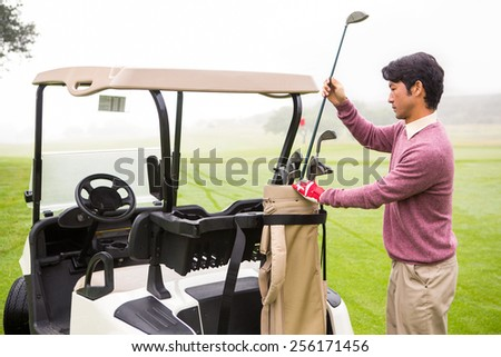 Golfer taking club in golf bag in golf course
