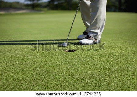 Golfer taps in a putt on a green