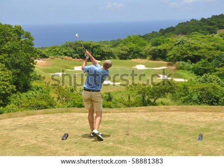 Golfer trying a par 3 on a course in Jamaica - stock photo