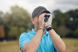 Golfer using a rangefinder to measure the distance to the hole holding it to his eye as he peers down the fairway in a close up head and shoulders for a healthy active lifestyle or sport concept