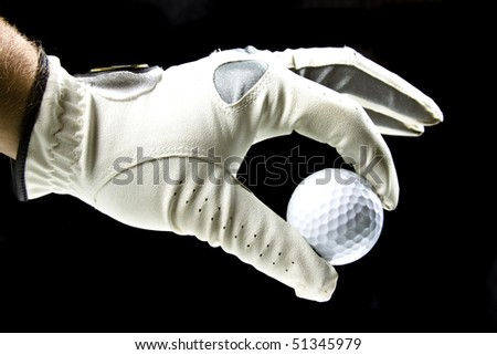 golfer wearing a golf glove holding a ball with his fingers isolated on black