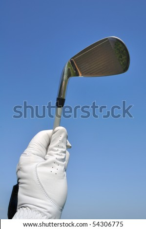 Golfer Wearing a Golf Glove Holding an Iron (Golf Club) Against a Blue Sky