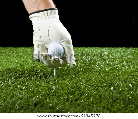 golfer wearing a golf glove putting a ball and a tee in the ground before teeing off, copy space.