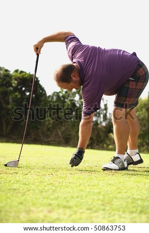 Golfer wearing a purple shirt getting ready to tee off.