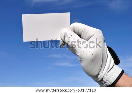 Golfer Wearing Golf Glove Holding a Blank Business Card Against a Blue Sky